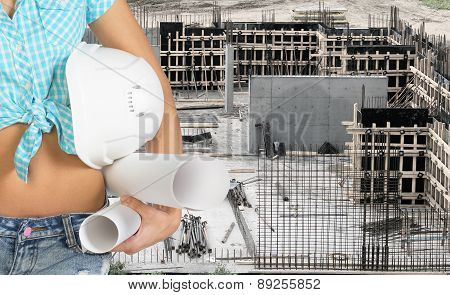 Smiling young woman holding hard hat and paper scrolls