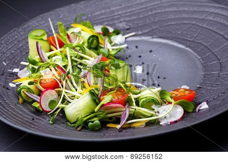 Authentic Fresh Vegetable Salad With Sprouts And Peas Black Pepper On A Black Plate. Morning Atmosph