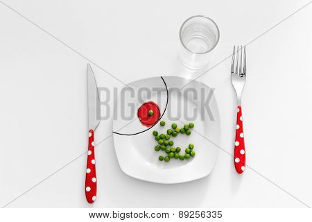 Peas on a plate with a glass of water, dieting concept