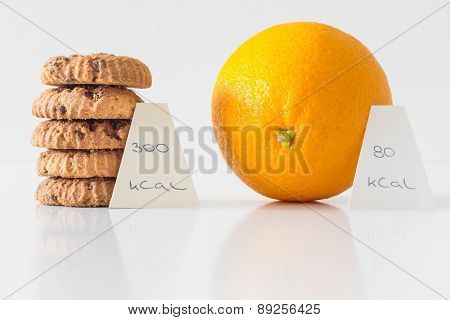 Cookies or orange fruit, diet choice concept, calorie count