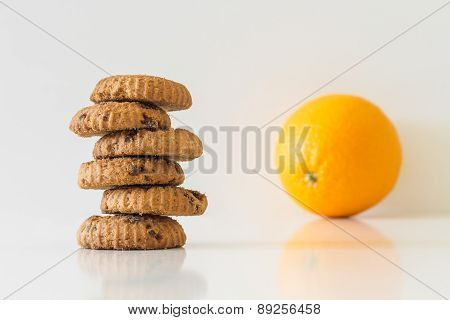 Cookies or fruit, cookies in focus, orange blurred, diet choice
