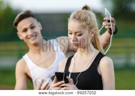 A Young Woman Looking Back On The Phone And Her Friend Who Laughs