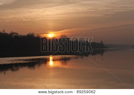 The sun rises over the misty river