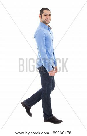 Side View Of Young Arabic Bearded Business Man In Blue Shirt Walking Isolated On White