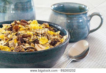 granola in a blue bowl ceramic mugs in the background