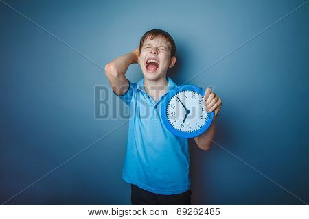 teenager boy brown European appearance holds a clock closed his