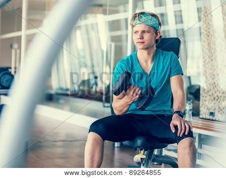 Young man in gym hall training with dumbbell