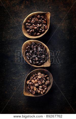 Top view of three different varieties of coffee beans on dark vintage background