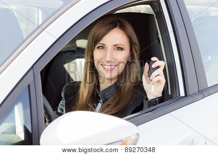 Young Smiling Woman In Car With Key In Hand.