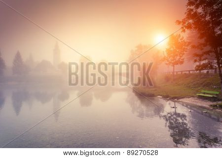 Majestic colorful foggy morning on the lake in Triglav national park, located in the Bohinj Valley of the Julian Alps. Dramatic view of the church St. John the Baptist. Slovenia, Europe. Beauty world.