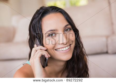 Pretty brunette calling with her mobile phone at home in the living room