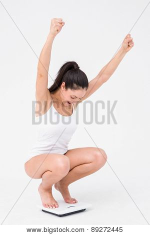 Beautiful woman cheering on weighing scales on white background