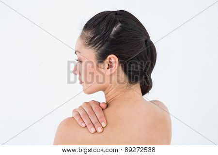 Brunette touching her painful shoulder on white background