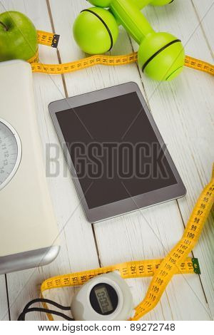 Tablet with indicators of healthy lifestyle on wooden table