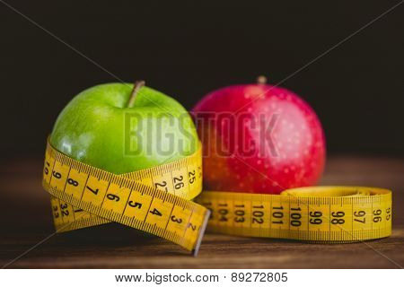 Green and red apples with measuring tape on wooden background
