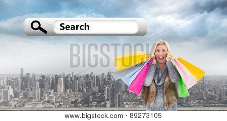 Blonde in winter clothes holding shopping bags against clouds over city