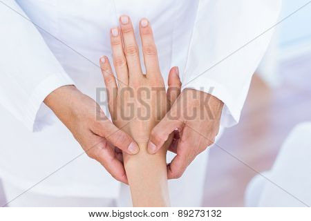 Doctor examining her patients wrist in medical office