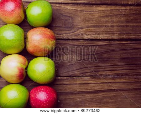 Fresh colorful apples on wooden background