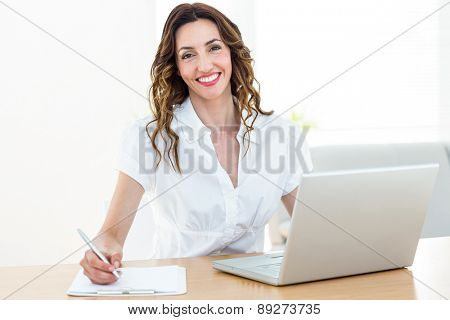 Smiling businesswoman working with her laptop and taking notes on white background