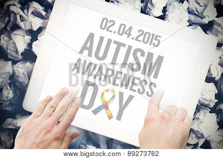 Autism awareness day against hands touching tablet screen