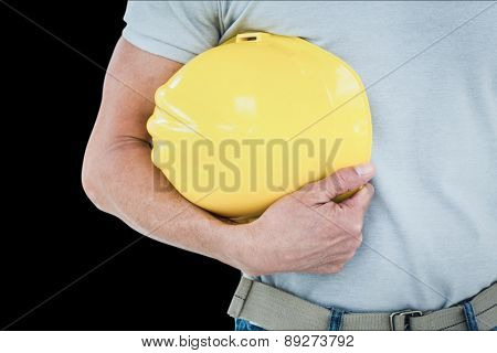Technician holding hard hat against black