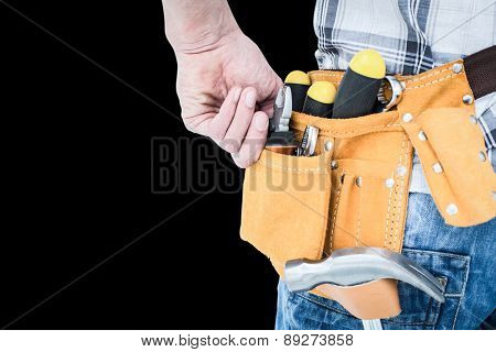 Technician with tool belt around waist against black