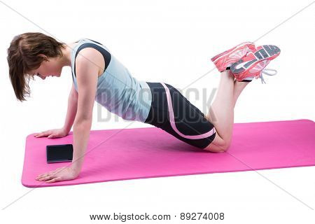Pretty brunette doing press up on fitness mat on white background
