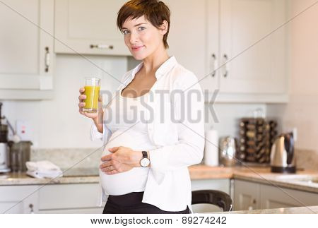 Pregnant woman having a glass of orange juice at home in the kitchen