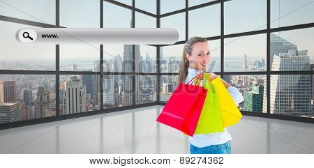 Smiling blonde holding shopping bags against room with large window showing city