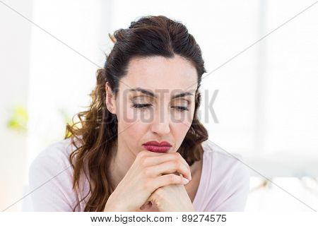 Upset brunette sitting on the couch on white background
