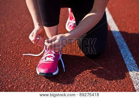 Girl ties laces on her sports shoes on running track. Horizontal photo