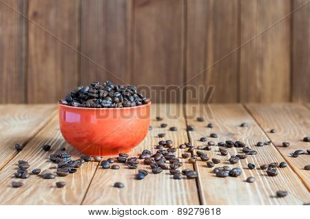 Coffee beans in red bowl on dark wooden background