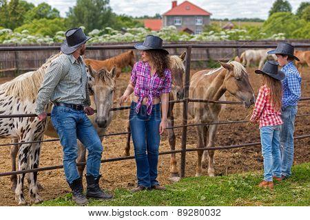 cowboy family of four feeding foals hay