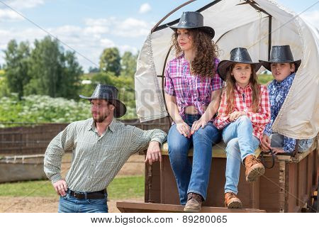 cowboy family of four in a wagon