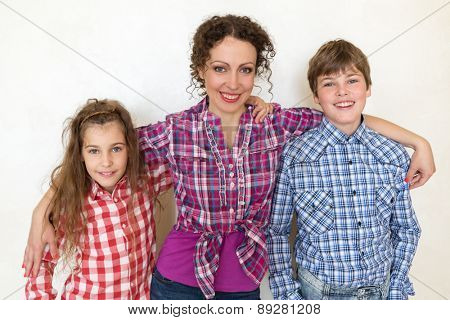 mother with two children posing on white background closeup