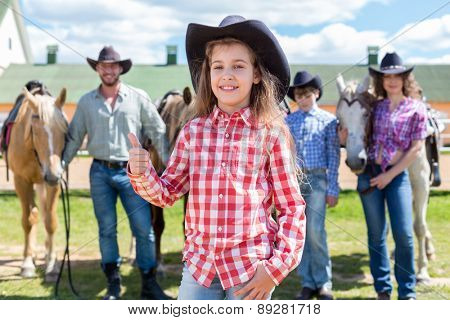 cowboy girl with ok gesture closeup portrait on background of her family with horses