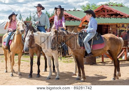 cowboy family of four on horses