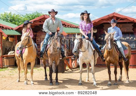 happy cowboy family of four on horsebacks waving their hands