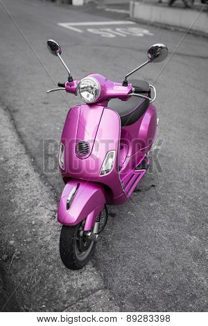 Pink italian scooter on the street