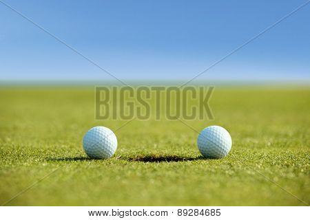 Golf balls near hole