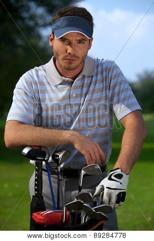 Portrait of young man standing by golf bag full of sticks
