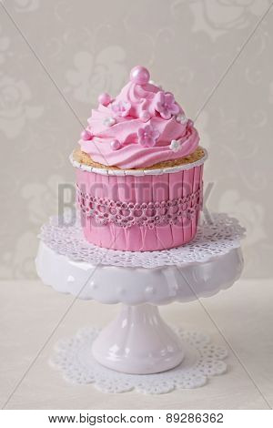 Pink cupcake on a beige background