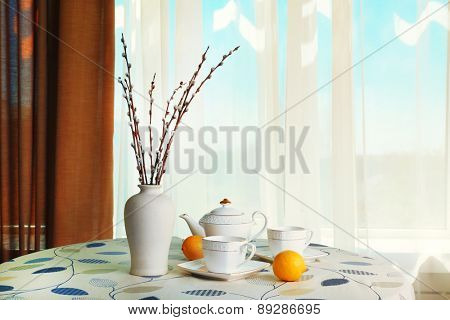 Willow twigs in vase with teapot, cups and lemon on table on curtains background