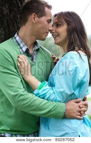 Happy young couple by tree