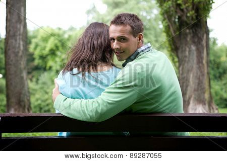 Portrait of young man with girlfriend sitting on bench