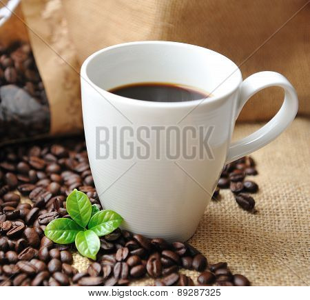 Cup of coffee with beans and leaf. Coffee theme