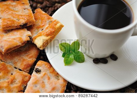 Cup of coffee and tasty cookie with coffee leaf
