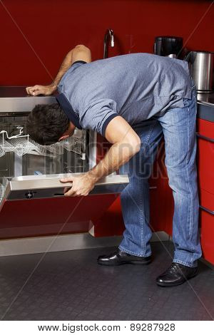 Young man looking at dish washer