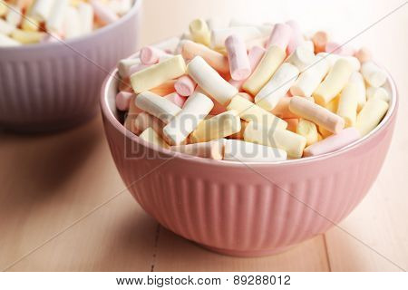 Sweet candies on color wooden table, closeup