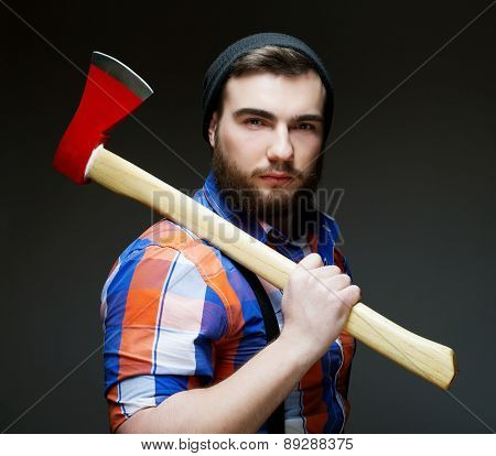 Young bearded man with  big axe on shoulder standing against dark  background